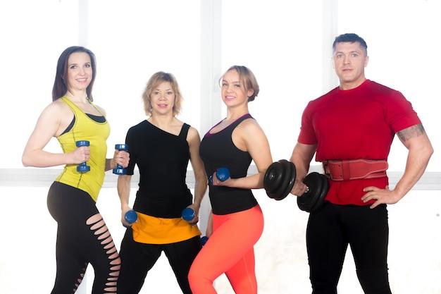 Equipe de pessoas esportivas positivas posando com dumbbells na academia