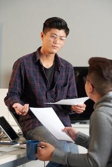 Equipe de programadores trabalhando no projeto que estão discutindo o documento la com especificações de requisitos ...