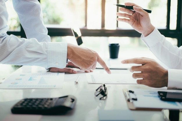 Equipe de projeto do negócio que trabalha junto no quarto de reunião no escritório.