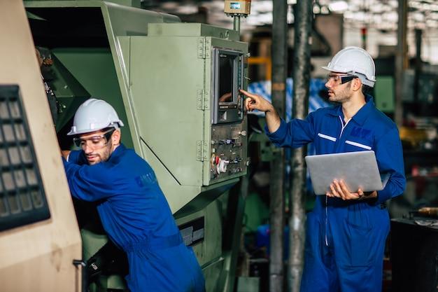 Equipe de serviço da máquina que verifica o processo de cnc e reprogramação durante a produção da fábrica.