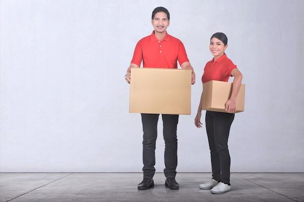 Equipe de serviço de entrega asiática atraente com caixa de papelão