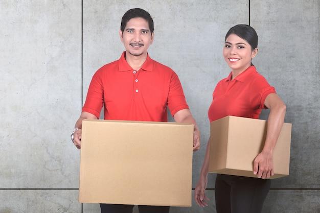 Equipe de serviço de entrega asiática jovem com a parcela de pé