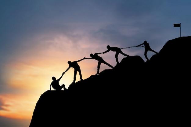 Equipe de silhueta de pessoas caminhando para o topo da montanha no pôr do sol