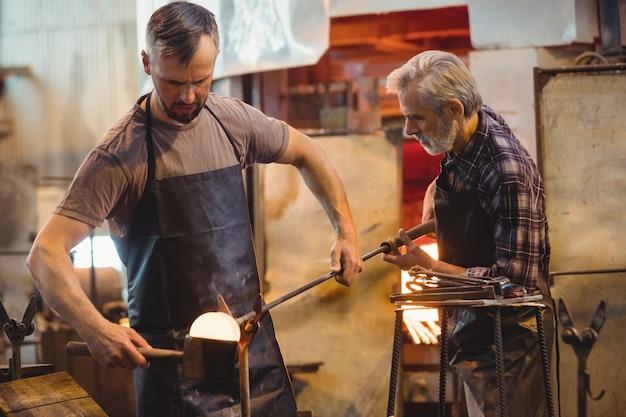 Equipe de soprador de vidro formando e moldando um vidro fundido