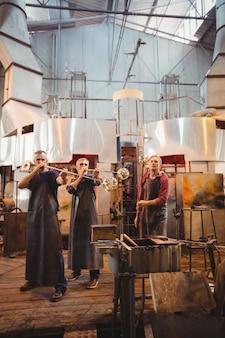 Equipe de soprador de vidro moldar um copo na zarabatana