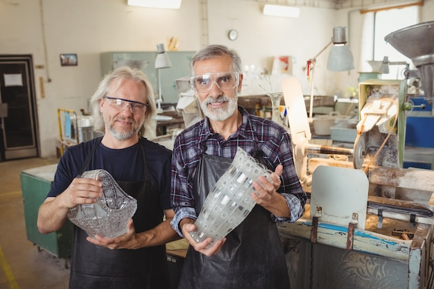 Equipe de sopradores de vidro com os braços cruzados