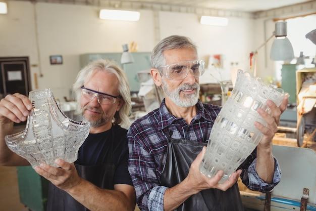 Equipe de sopradores de vidro examinando vidro