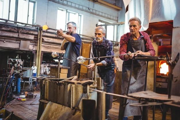 Equipe de sopradores de vidro moldar um copo na zarabatana