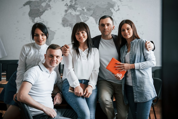 Equipe de sucesso de jovens freelancers posando para a fotografia depois do trabalho