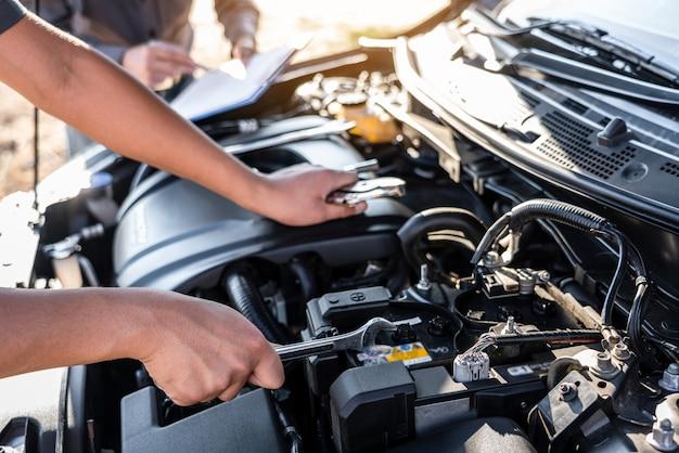 Equipe de técnicos trabalhando de mecânico de automóveis em fazer serviço de reparo de automóveis e trabalhador de manutenção reparando veículo com chave, serviço e verificação de carro de manutenção.