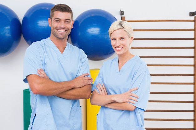 Equipe de terapeutas com braços cruzados sorrindo para a câmera