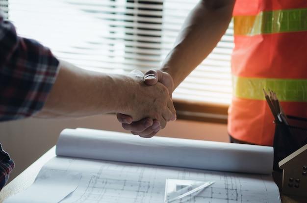 Equipe, de, trabalhador construção, apertando mãos, com, cliente