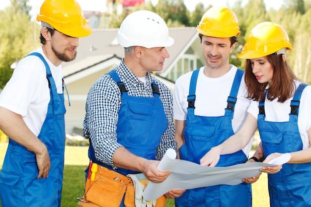 Equipe de trabalhadores analisando o projeto da casa
