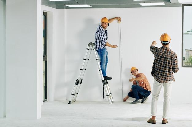Equipe de trabalhadores da construção civil em capacetes medindo a parede com fita métrica