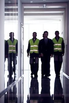 Equipe de trabalhadores e gerente caminhando no corredor da fábrica Foto Premium