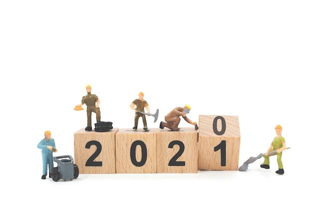 Equipe de trabalhadores em miniatura construindo bloco de madeira número 2021