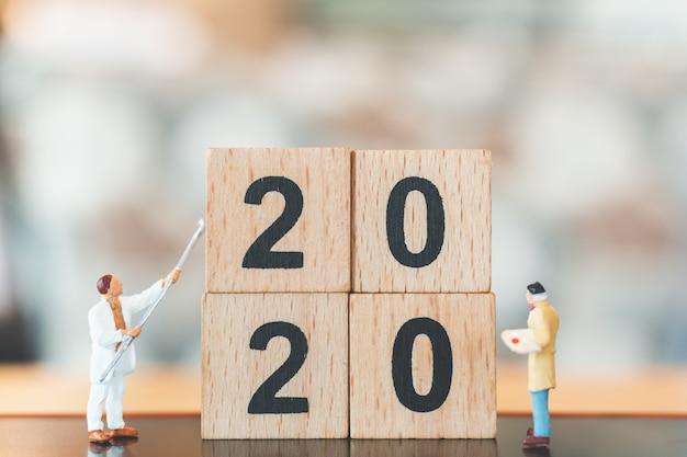 Equipe de trabalhadores em miniatura pintada no número de bloco de madeira 2020