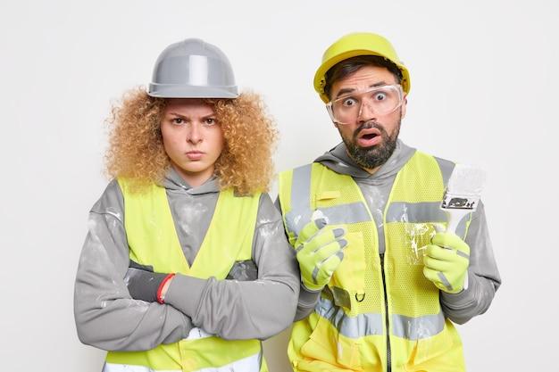 Equipe de trabalhadores industriais de mulher e homem vestidos de uniforme recebe instruções do empregador segura equipamentos de construção.