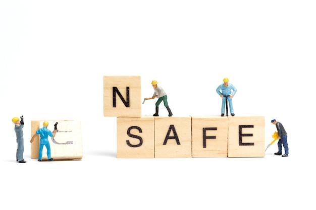Equipe de trabalho de pessoas em miniatura mudando a palavra inseguro se transformou em seguro em fundo branco