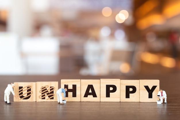 Equipe de trabalho de pessoas em miniatura na palavra infeliz em letras do alfabeto de madeira com o prefixo un riscado, deixando a palavra feliz