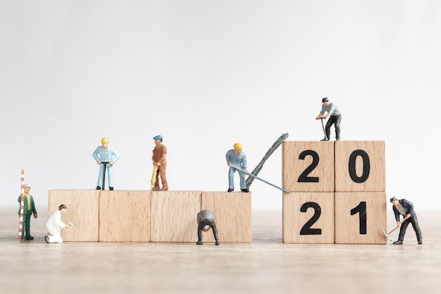 Equipe de trabalho em miniatura criar número 2021