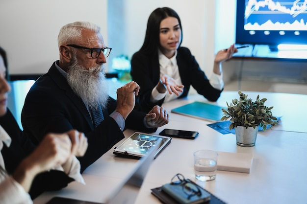 Equipe de trader de negócios fazendo análise de blockchain dentro do escritório de fundos de hedge - foco principal na mão esquerda da mulher