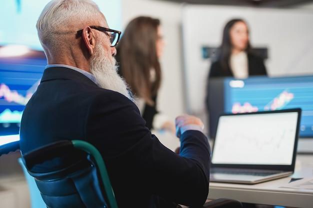 Equipe de trader fazendo conferência de análise de mercado de ações dentro do escritório de fundos de hedge - foco no rosto de um homem sênior sentado em uma cadeira de rodas