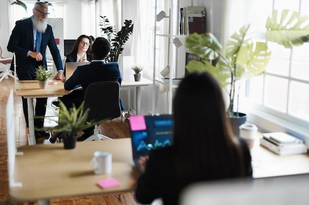Equipe de trader multirracial fazendo análise do mercado de ações dentro do escritório de fundos de hedge - foco no rosto da mulher madura