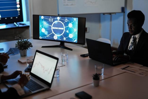 Equipe de traders multirraciais fazendo pesquisa de blockchain dentro do escritório de fundos de hedge