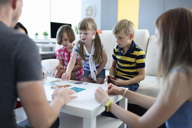 Equipe de três crianças e equipe de três adultos jogam jogos de tabuleiro em casa