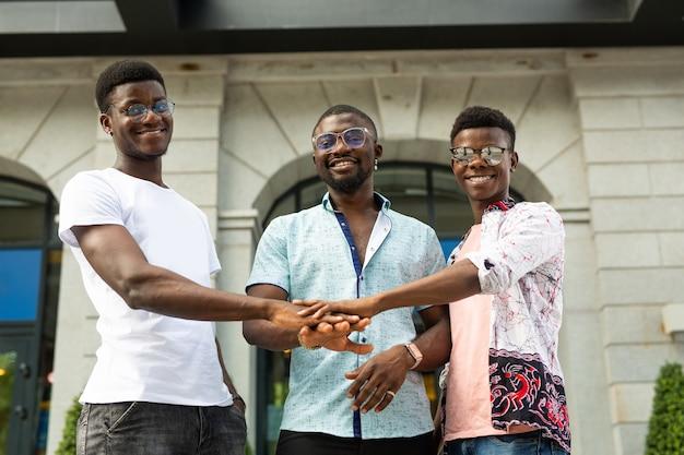 Equipe de três jovens africanos apertando as mãos