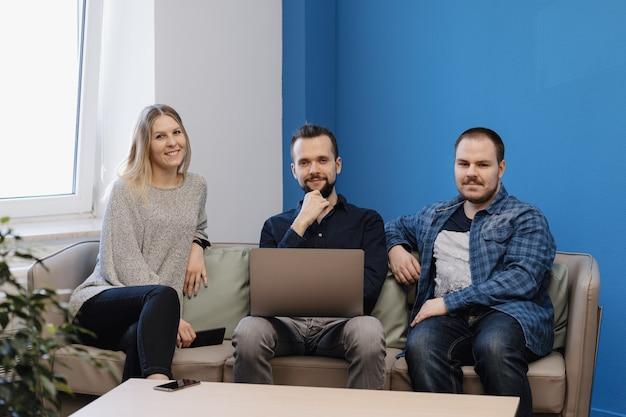 Equipe de três pessoas trabalhando no laptop no escritório no sofá