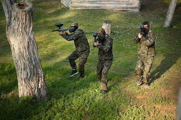 Equipe de uniforme e máscaras jogando paintball, batalha no playground da floresta. esporte radical com arma pneumática e balas ou marcadores de tinta, jogo militar ao ar livre, táticas de combate