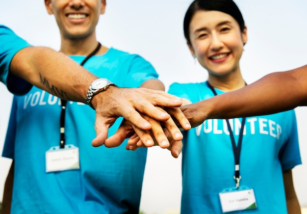 Equipe, de, voluntários, empilhando mãos