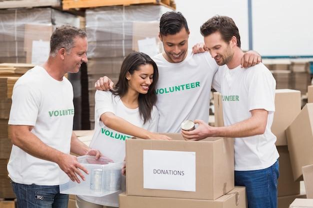 Equipe de voluntários que embala uma caixa de doação de alimentos