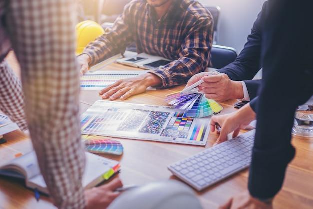 Equipe designer trabalhando gráfico com cartela de cores e reunião de brainstorm para novo projeto.