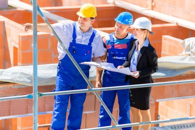 Equipe discutindo construção ou construção de planos de site