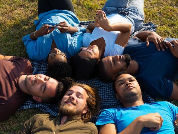 Equipe diversificada de amigos relaxantes no parque