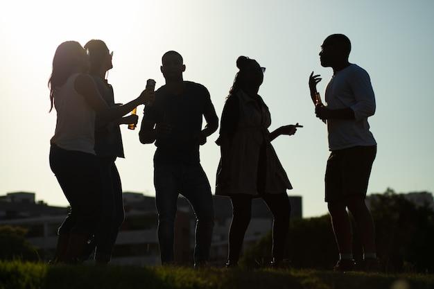 Equipe diversificada de amigos se divertindo na festa ao ar livre