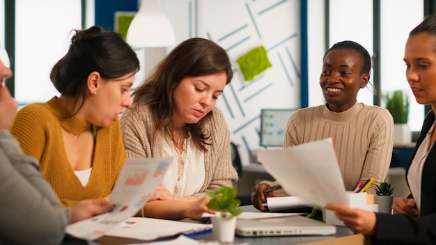Equipe diversificada de colegas de trabalho profissionais, brainstorming em uma reunião de negócios sob o olhar atento do chefe africano. empresa de diretor negro avaliando funcionários sentados à mesa discutindo