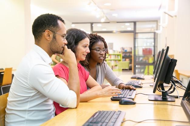 Equipe diversificada de estudantes adultos trabalhando juntos