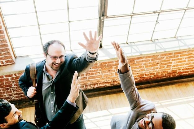Equipe diversificada de negócios levantando as mãos para o alto