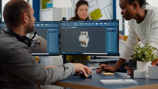 Equipe diversificada discutindo sobre projeto industrial usando monitores duplos