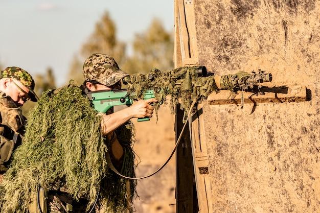 Equipe do atirador armado com calibre grande, rifle sniper, atirando em alvos inimigos ao alcance do abrigo, sentado em uma emboscada