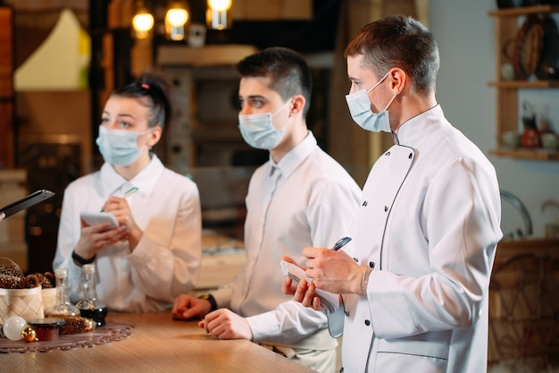 Equipe do café em briefing matinal usando máscaras de proteção