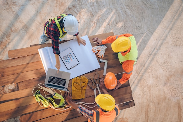 Equipe do coordenador e dos arquitetos que trabalham, reunião, discussão, projeto, planejamento, medindo a disposição de modelos de construção no canteiro de obras, vista superior, conceito da construção.