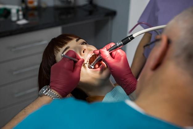 Equipe do dentista médico no consultório odontológico moderno, fazendo o tratamento do dente para o paciente jovem do sexo feminino. dentista masculino sênior e seu assistente no fundo