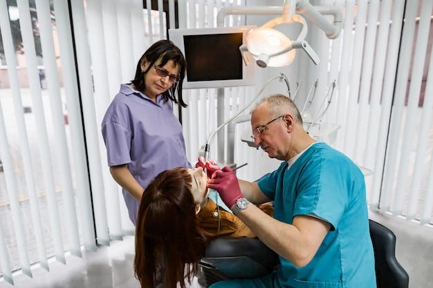 Equipe do dentista médico no consultório odontológico moderno, fazendo o tratamento do dente para o paciente jovem do sexo feminino. dentista masculino sênior e seu assistente trabalhando na clínica odontológica moderna