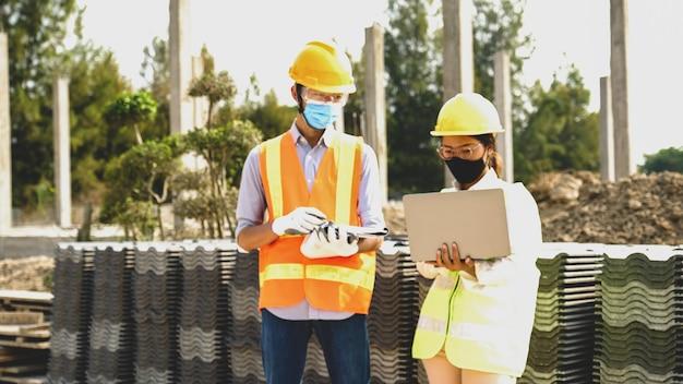 Equipe do empreiteiro do engenheiro reunindo-se com o projeto do plano de trabalho da indústria e verificar o projeto no canteiro de obras