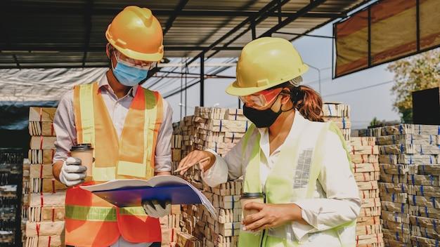 Equipe do empreiteiro do engenheiro reunindo-se com o projeto do plano de trabalho da indústria e verificar o projeto no local de construção